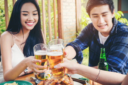 Group of young asian people celebrating beer festivals happy while enjoying home party Stock Photo