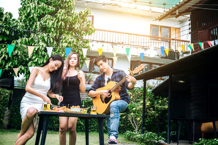 Group of young asian people happy while enjoying home party and play guitar on garden home Stockfoto