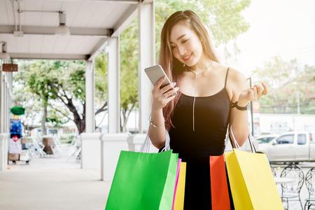Woman using phone enjoying shopping Street