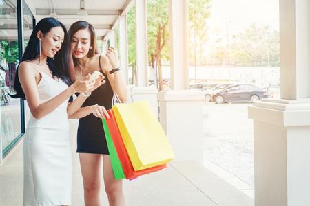Happy women using phone Enjoying Spending shopping bags in Fashion shopping street Stock Photo