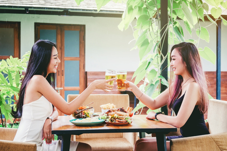 Young asian women drinking beer and clink glasses happy while enjoying home party Stock Photo