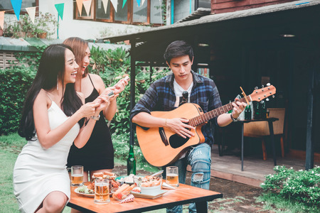 Group of young asian people happy while enjoying home party and play guitar on garden home Stock Photo