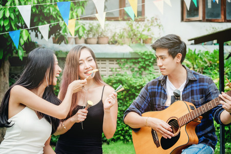 Group of young asian people happy while enjoying home party and play guitar on garden party