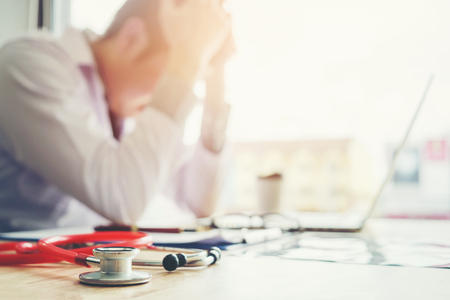 Stethoscope and doctor sitting with laptop stress headache about work in hospital Stock Photo