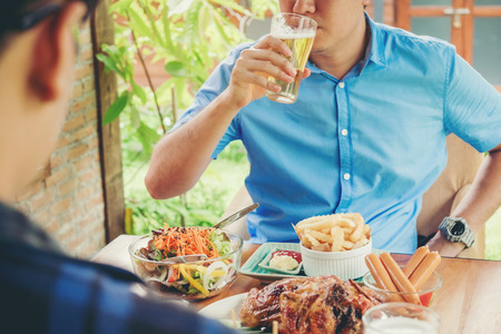 Young asian mans drinking beer and eatting foods happy while enjoying home Stock Photo