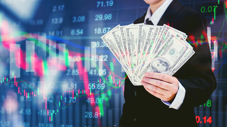 돈을 들고 사업가 디지털 주식 시장 금융 exchange 정보 및 무역 그래프 배경에 달러 지폐