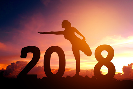 Silhouette young woman practicing yoga on 2018 new year