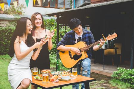 小组年轻亚裔人民愉快,当享受庭院党和在庭院家庭的吉他