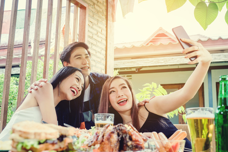 Group of friends are taking selfie and eating food are happy enjoying in home Stock Photo