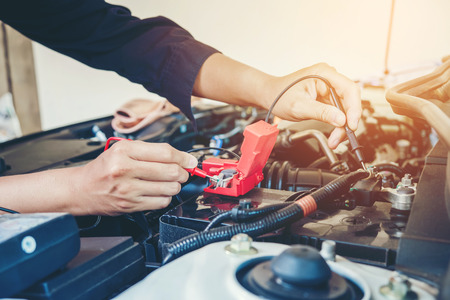 Hands check battery car mechanic working in auto repair service Stockfoto
