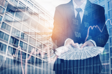 Businessman Holding money US dollar bills on digital stock market financial exchange and Trading graph Double exposure city on the background Stock Photo