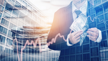 Businessman Holding money US dollar bills on digital stock market financial exchange and Trading graph Double exposure city on the background Zdjęcie Seryjne