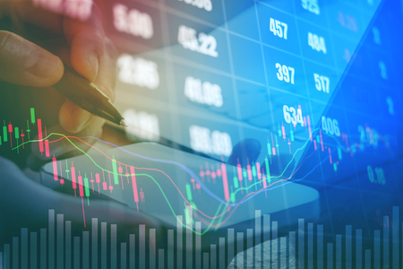 Businessman writing the trading graph of stock market on digital stock market financial exchange and Trading graph
