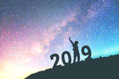 Silhouette young man Happy for 2019 new year background on  the Milky Way galaxy pointing on a bright star. dark sky tone . Vintage grain tone. Standard-Bild
