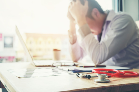 Stethoscope and doctor sitting with laptop stress headache about work in hospital Standard-Bild