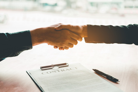 Business people negotiating a contract handshake between two colleagues