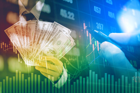 Businessman Holding money US dollar bills on digital stock market financial exchange information and Trading graph background Stock Photo