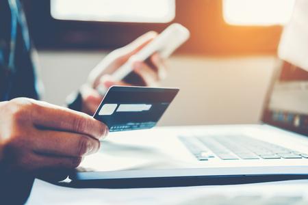 Hombre que sostiene la tarjeta de crédito y que usa el teléfono celular que sostiene la tarjeta de crédito con compras en línea