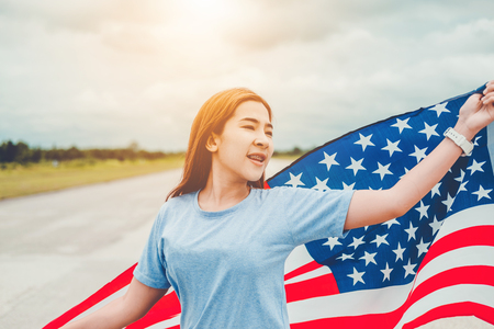 Happy woman standing with American flag Patriotic holiday.USA celebrate 4th of July Stock Photo