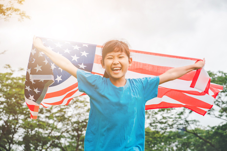 Happy kid little child running with American flag USA celebrate 4th of July Stock Photo