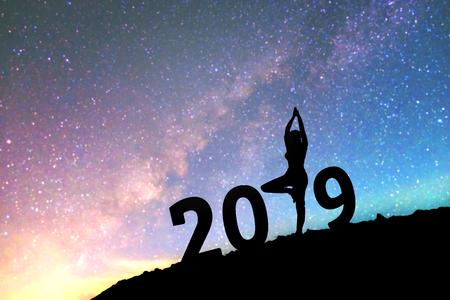 Silhouette junge Frau Happy Yoga für 2019 Neujahr Hintergrund auf der Milchstraße Galaxie