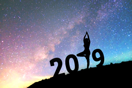 Silhouette young woman Happy yoga for 2019 new year background on  the Milky Way galaxy