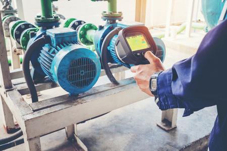 Técnico en termografía dando servicio a una torre de enfriamiento de motor de agua en la fábrica. Foto de archivo