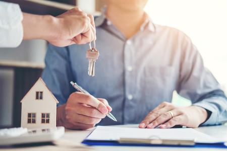 Agente de venta que entrega las llaves de la casa al cliente y firma el contrato de acuerdo, concepto de seguro de hogar Foto de archivo