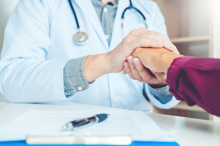 Doctor holding hands for comforting and care patient