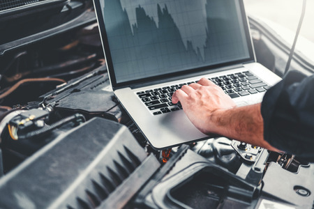Professional Technician Hands of checking car engine repair service using laptop on car Stock Photo