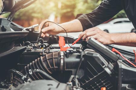 Mecánico de automóviles que trabaja en el garaje Técnico Manos del mecánico de automóviles que trabajan en reparación de automóviles Servicio y mantenimiento Comprobación de la batería del automóvil. Foto de archivo