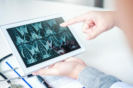 Médico que consulta con el paciente que presenta los resultados de la película de rayos X en la tableta digital sentado en la mesa Foto de archivo