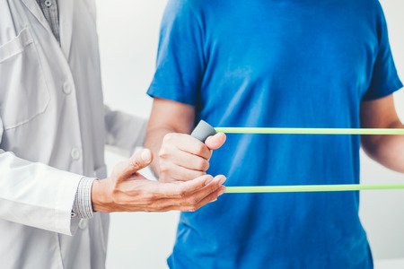 Physiotherapist man giving resistance band exercise treatment About Chest muscles and Shoulder of athlete male patient Physical therapy concept