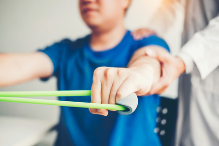 Physiotherapist man giving resistance band exercise treatment About Arm and Shoulder of athlete male patient Physical therapy concept Stock Photo