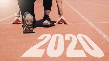 Año Nuevo 2020, Mujer Atleta comenzando en línea para comenzar a correr con el número 2020 Comienzo al año nuevo.