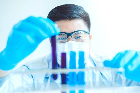 Scientist with equipment holding tools during scientific experiment science concept