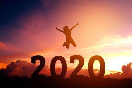 2020 Newyear Silhouette młoda kobieta skacze do koncepcji szczęśliwego nowego roku.