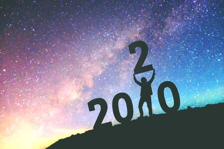 2020 Newyear Man tries to Lift up number of 2020 Happy new year background on  the Milky Way galaxy