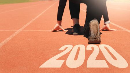 2020 Newyear , Athlete Woman starting on line for start running with number 2020 Start to new year.
