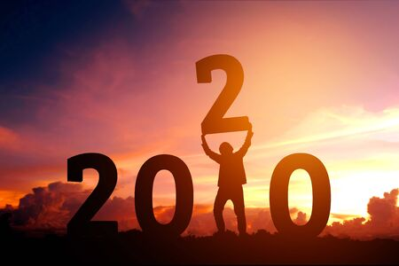 2020 Newyear Man tries to Lift up number of 2020 Happy new year concept 스톡 콘텐츠