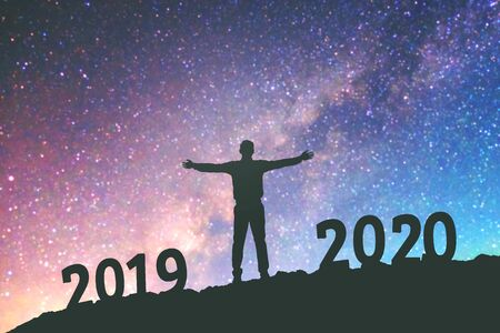 Silhouette young Business man happy to 2020 new year success background on  the Milky Way galaxy