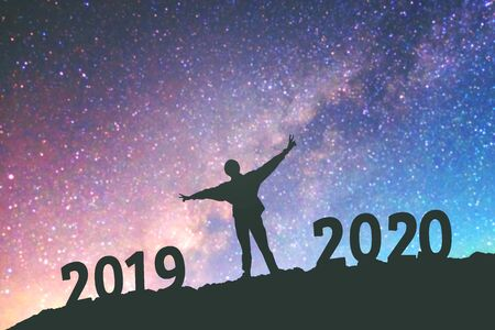 Silhouette young man Happy for 2020 new year background on  the Milky Way galaxy