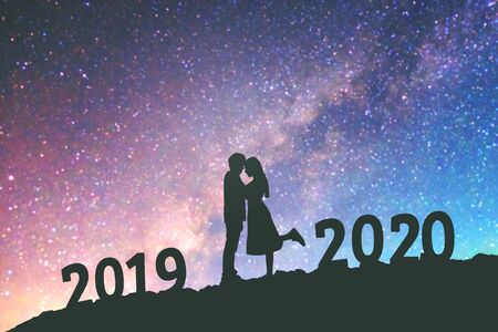2020 Newyear Silhouette young couple Happy for romantic background on the Milky Way galaxy pointing on a bright star.