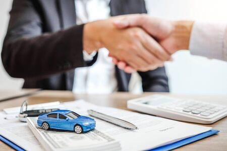 Sale agent handshake deal to agreement successful car loan contract with customer and sign agreement contract  Insurance car concept.