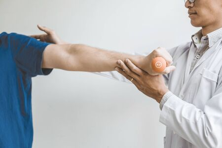 Physiotherapist man giving exercise with dumbbell treatment About Arm and Shoulder of athlete male patient Physical therapy concept Reklamní fotografie
