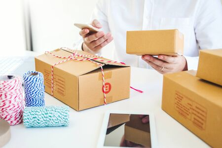SME freelance man working with packaging startup entrepreneur small business owner at home,Online business seller packaging and delivery concept Banco de Imagens