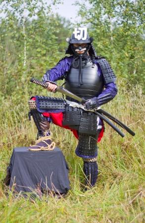 Man in Japanese medieval samurai armor  tosei-gusoku  pulling out katana sword Stock Photo
