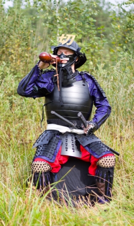 Man in Japanese medieval samurai armor (tosei-gusoku) with swords sitting outdoor drinking from brown gourd flask (hyotan) Stock Photo - 15152893