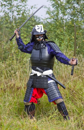 Man in Japanese medieval samurai armor (tosei-gusoku) standing in combat position with two swords (katana and vakizashi) photo