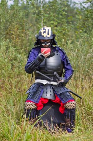 samoerai: Man in Japanse middeleeuwse samurai armor (Tosei-gusoku) met zwaarden zitten buiten drinken uit roze chawan joelen